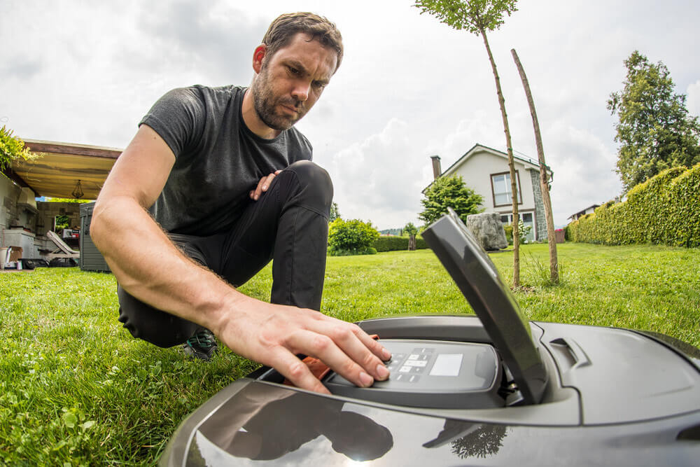 Young caucasian male is setting a robotic mower while kneeling in a nice green garden with blue skies